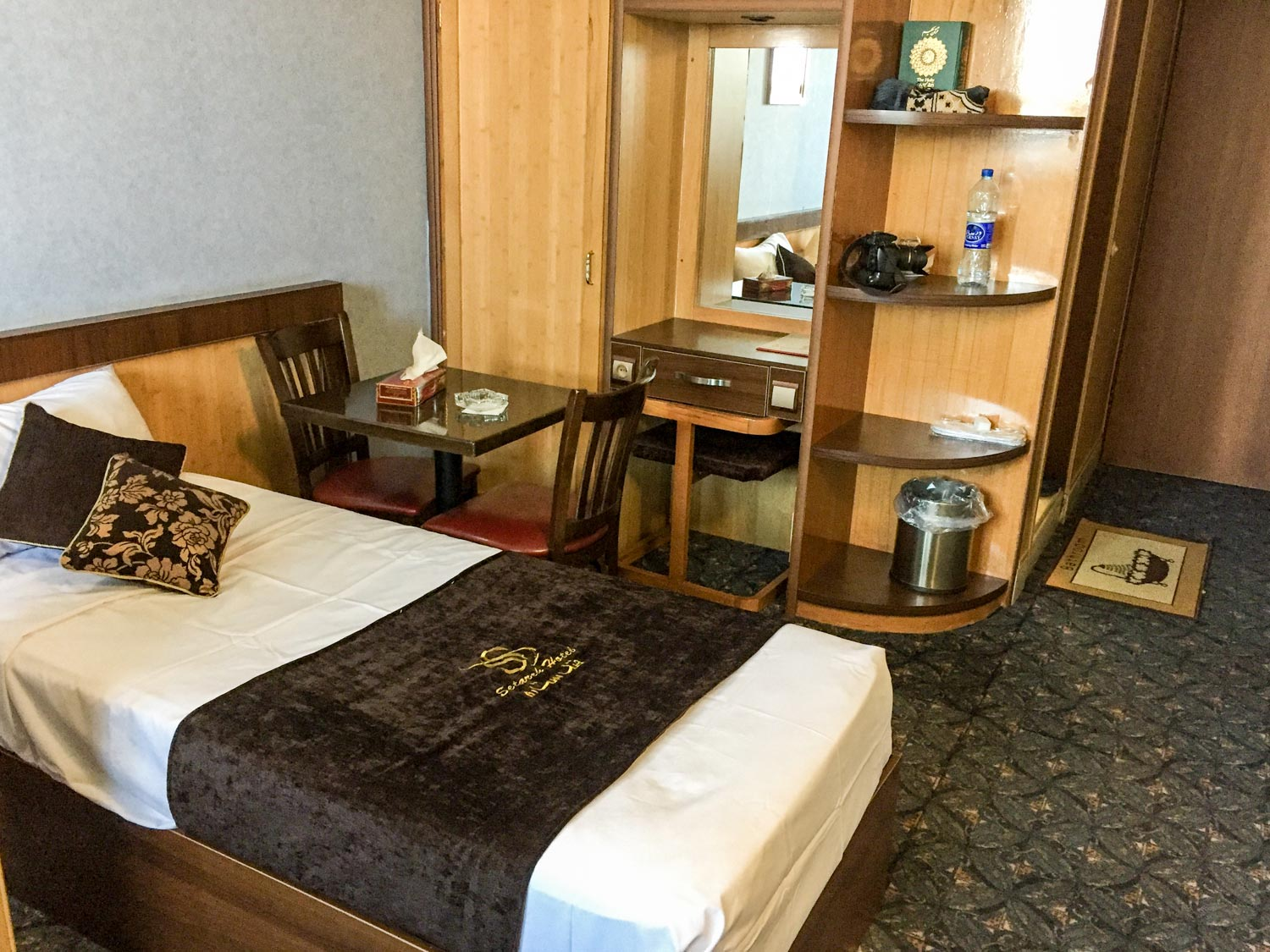 Setarah Hotel Isfahan room with a clean bed and shelves
