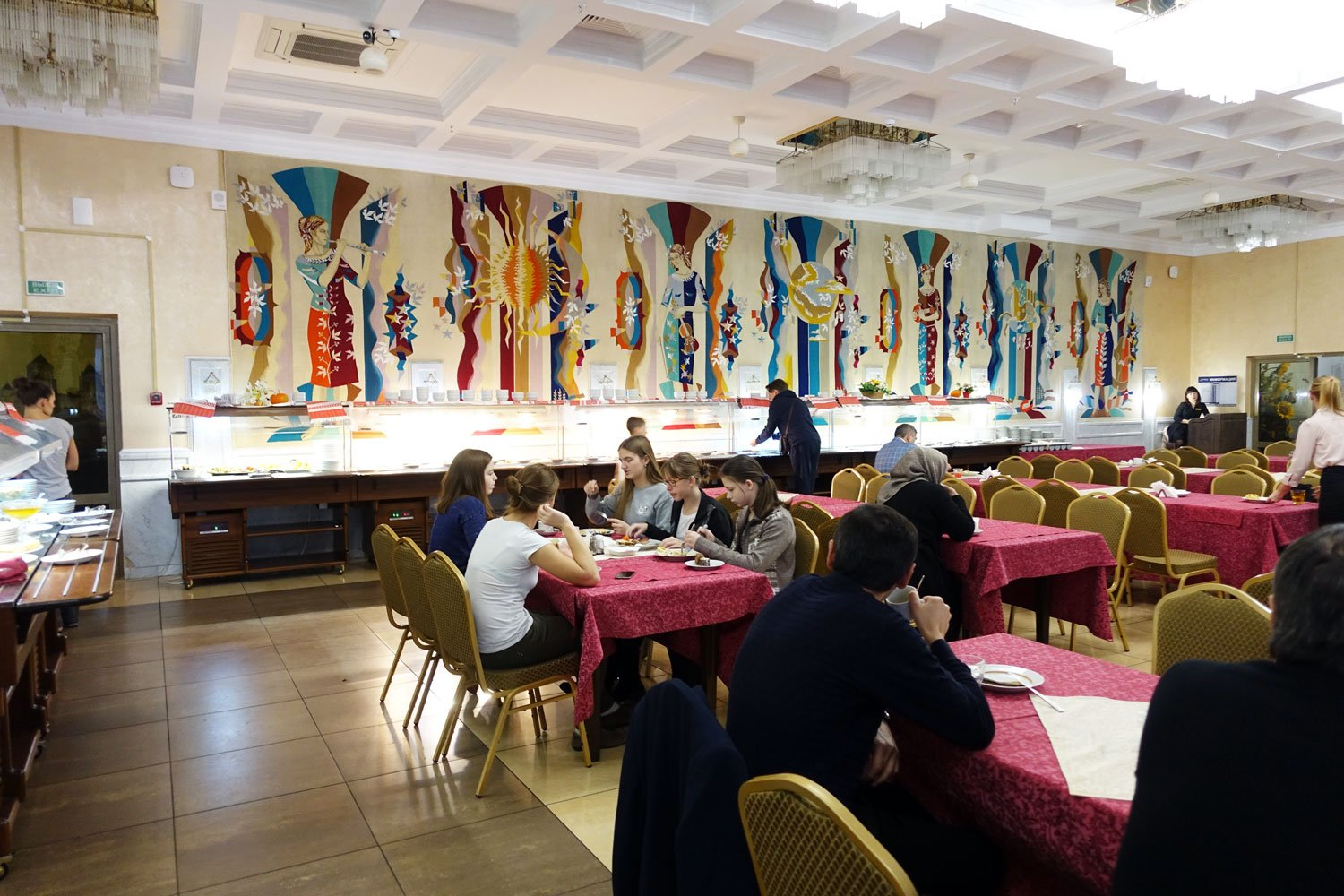 The breakfast hall at the hotel belarus with several people eating.